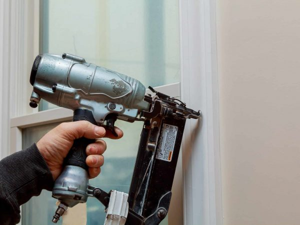 Mann hält Druckluftnagler an Fensterrahmen