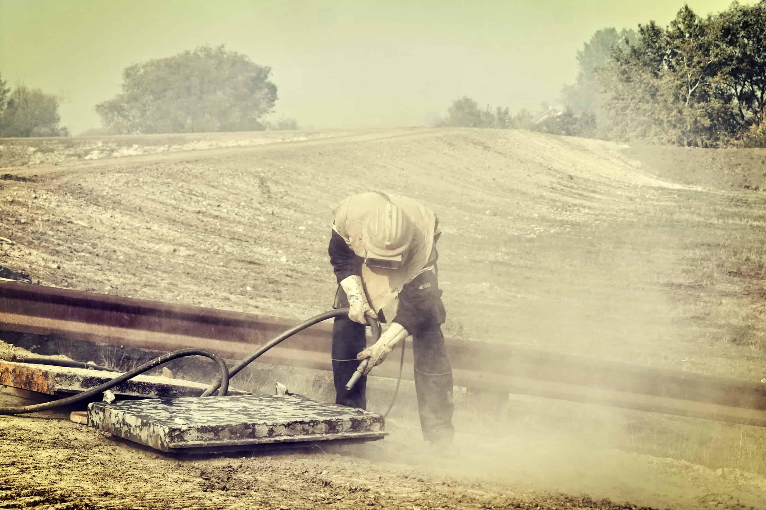 Mann arbeitet mit Sandstrahlgerät