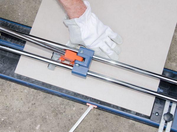 Laying floor tiles, tiler using a tile cutter