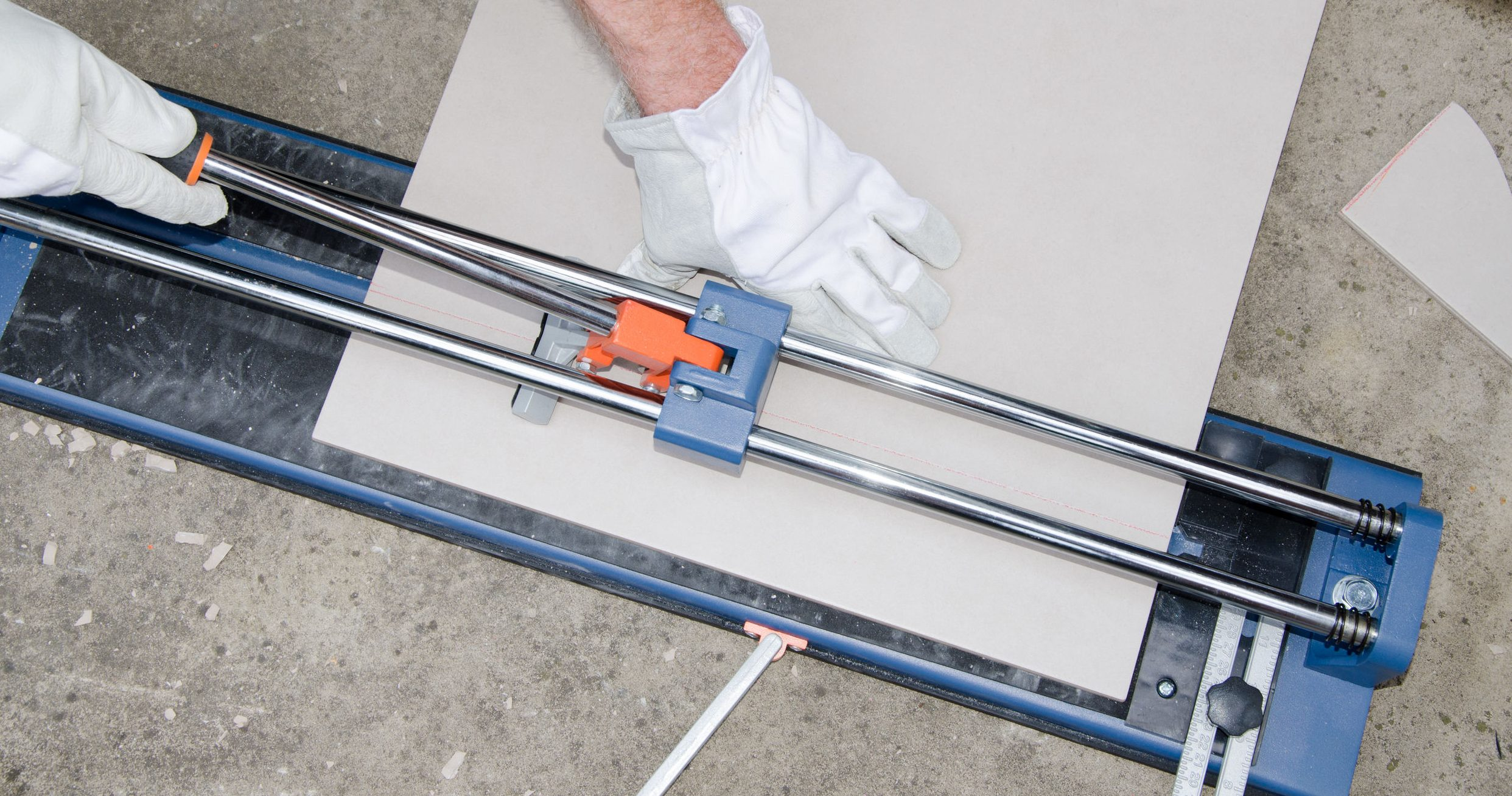 Laying floor tiles, tiler using a tile cutter