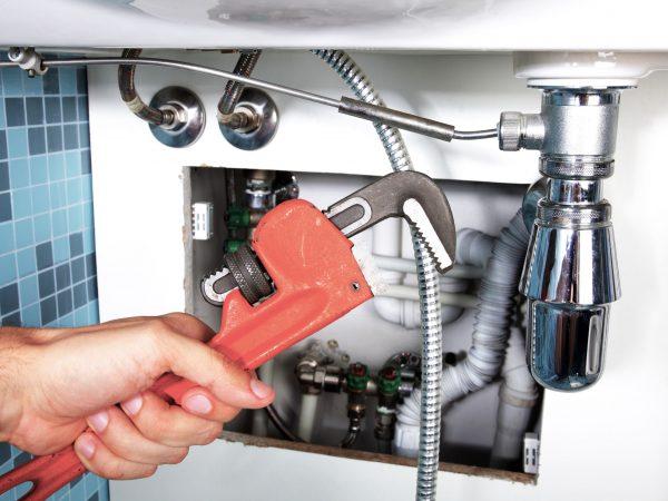 Plumbing work and sanitary engineering repairing a pipe under a sink. Sanitary works. Plumber repairing